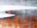 Vinterstemning ved elv med åpent vann. Kontrast mellom kaldt og varmt lys fra skog speiler seg i vannet. Frostrøyk gir kalst slør over elva en kald vinterdag i Januar. Glomma Askim. Østfold